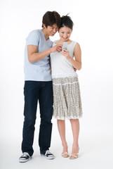 携帯電話を見る20代のカップル