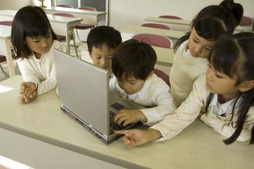 ノートパソコンを触る小学生