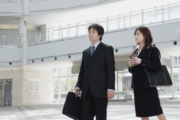 オフィスビルのロビーを歩く男性と女性