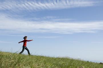 草原をスキップする女性