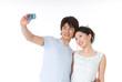 携帯で写真を撮る20代のカップル