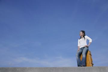防波堤でトランクの上に座る女性