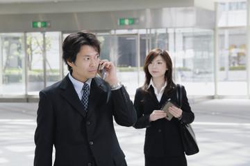 携帯電話で話す男性と女性