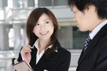 手帳を見ながら会話をする男性と女性
