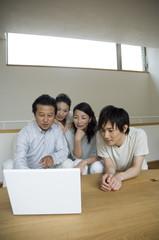 パソコンを見る中年夫婦と子供たち