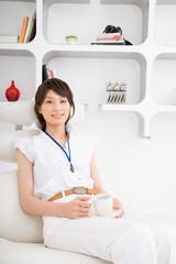 コーヒーを手に休憩する若い女性