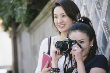 なまこ壁の前でカメラを構える女性2人