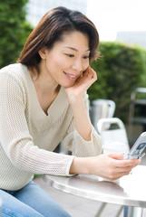 オープンカフェで携帯電話を眺める女性
