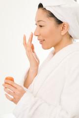 クリームを顔に塗るバスローブ姿の女性