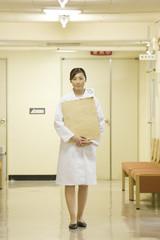 レントゲン写真を持ち廊下に立つ女性医師