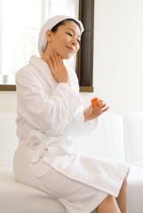 首筋をマッサージするバスローブ姿の女性