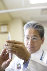 注射器を持つ医師