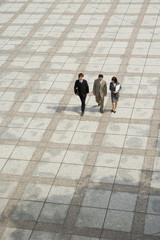 オフィス街のアトリウムと歩く男女3人