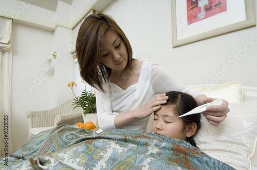 娘の熱をはかる母親
