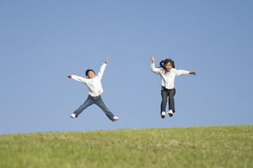 公園でジャンプする男の子と女の子