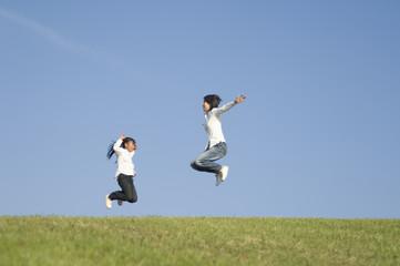 公園でジャンプする親子