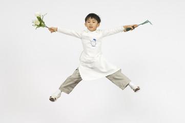 花とフォークを持つエプロンをした男の子