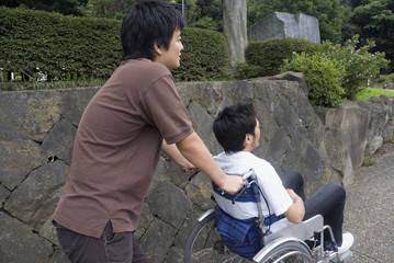 車椅子を押す若者