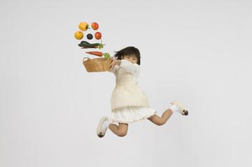 カゴを持つ小学生の女の子と飛び出る野菜