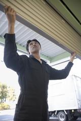 倉庫のシャッターを開ける若い男性