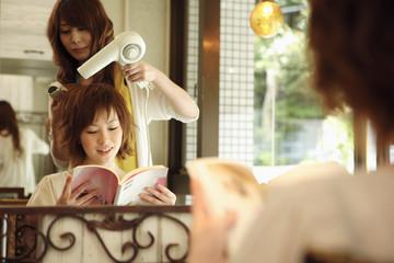 髪をブローされる女性