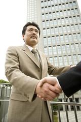 屋外で握手をする男性
