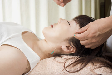 女性の顔や首に美容鍼を打つ