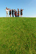 group of musicians play violins on hill against sky