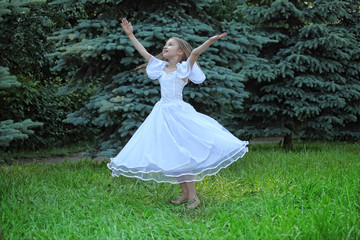 girl in white dress dances on lawn with lifted hands