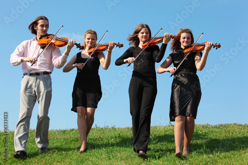 Four musicians go and playing violins against sky, front view