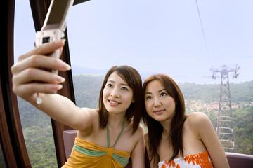 ロープウェーで携帯電話で撮影する女性二人
