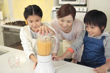 ジューサーを使う母親と子供2人