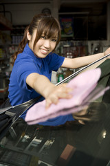 車の窓を拭く女性店員
