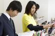 立ち読みをする高校生と雑誌を整理する女性店員