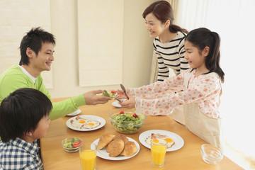 朝食を囲む家族4人