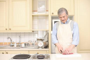 キッチンで料理をするシニア男性