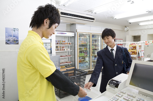 会計をする男性店員と高校生
