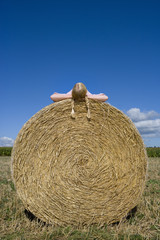 Girl (11-13) lying atop bale of hay in field