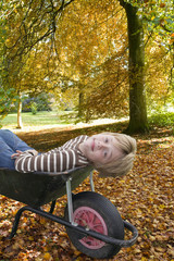 Young boy reclining in wheelbarrow in autumn