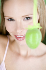 A young blonde woman holding a green Easter egg, close-up