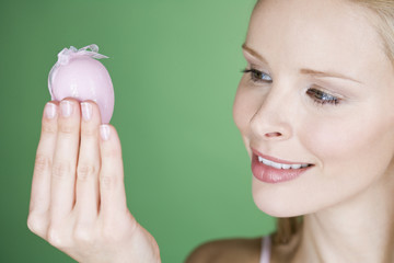 A young woman looking at a pink Easter egg