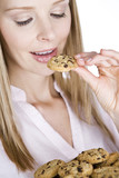 A young blonde woman eating a cookie