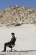 Businessman Sitting on Chair in the Desert