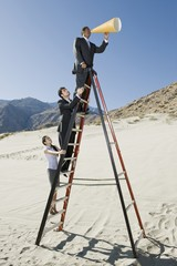 Business People on Stepladder Using Megaphone in Desert