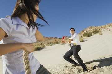 Two Business People Playing Tug of war in the Desert