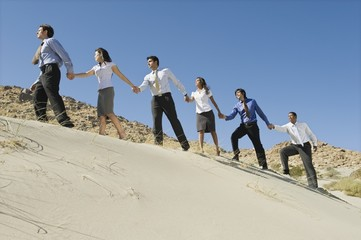 Business people holding hands while walking uphill in the desert.