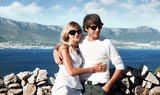 smiling young couple with sunglasses on a vacation trip poster