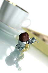 Cup of coffee and chocolates on a white background