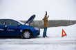 Stranded woman flagging down car in snow