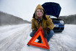 Stranded woman placing caution sign near car
